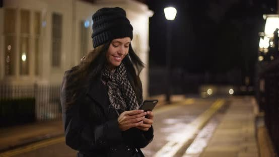 Thumbnail for Pretty Caucasian girl texting on her smartphone outdoors
