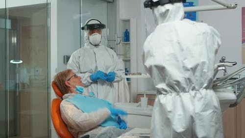 Doctor with Protective Mask Doing Hygienic Cleaning of Teeth