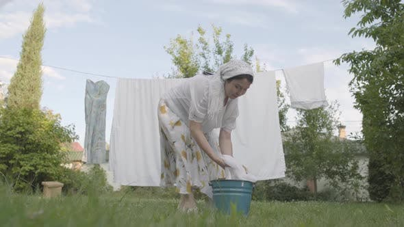 Thumbnail for Attractive Senior Woman with a White Shawl on Her Head Hanging Bed Linen on the Rope in the Garden