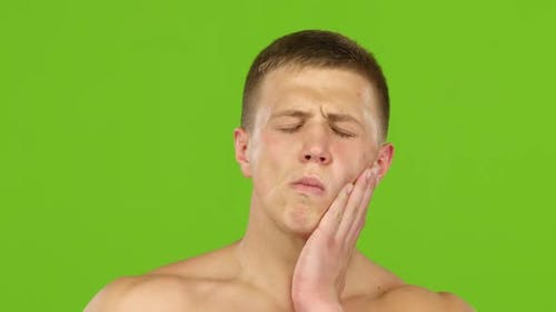 Man Suffers From Toothache and Rubs Jaw with Hand