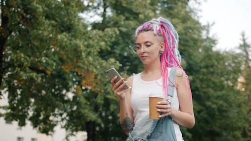 Nettes Mädchen Punk im Freien im Park mit Smartphone spazieren und Kaffee herausnehmen