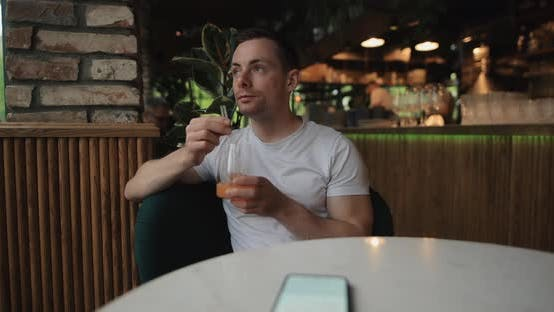 Man Drinks Fruity Juice in Restaurant