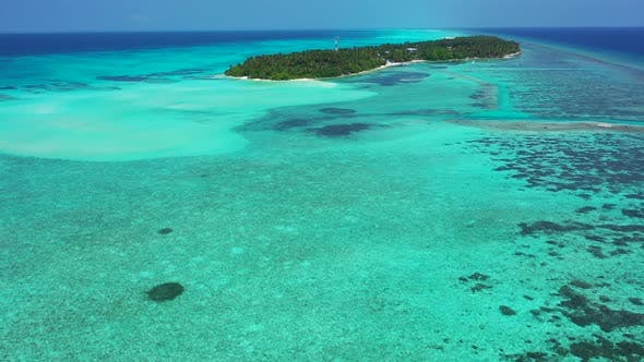 Wide flying travel shot of a white sandy paradise beach and aqua turquoise water background in vibra