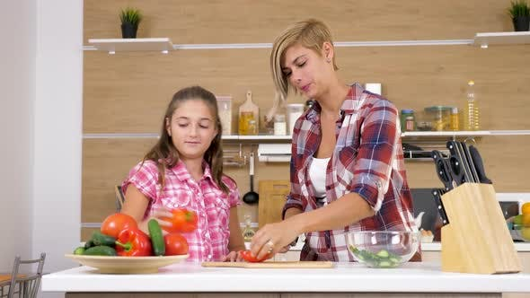 Mother and Daughter at the Kitchen Cutting a Sweet Red Peper