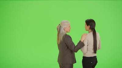 A professor advises a student on green screen