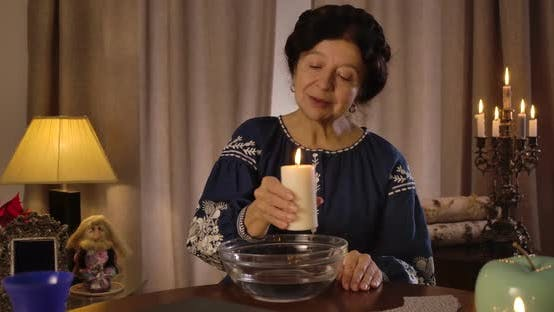 Thumbnail for Mature Caucasian Woman Holding Big Candle and Moving It Around Plate with Water