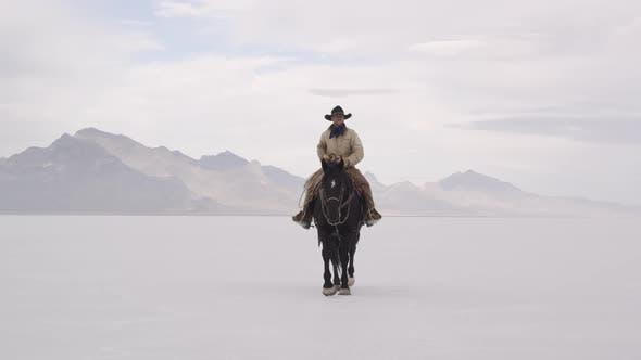 Cowboy riding horse on salt flats.