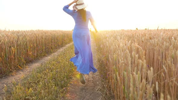 Beautiful Woman in a Blue Dress and Hat Runs Through a Wheat Field at Sunset. Freedom Concept. Wheat