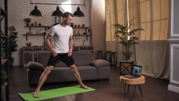 Fit Man Practices Yoga mit Online-Trainer Indoor