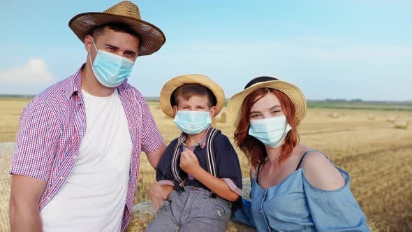 Happy Family Wearing Medical Masks Observe Safety Precautions While Walking in Field with Bales