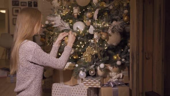 Ein junges Mädchen schmückt einen Weihnachtsbaum. Konzept - Frohe Weihnachten, Neujahr