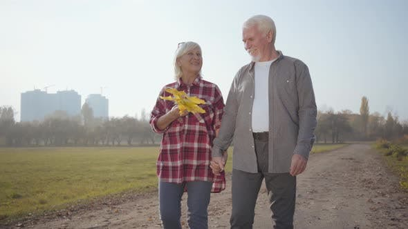 Thumbnail for Laughing Mature Caucasian Couple Strolling in the Autumn Evening and Talking. Happy European Senior