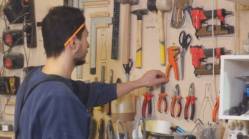 Young Carpenter in Uniform Selects a Suitable Tool for Wood Work