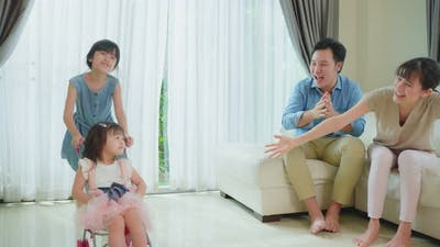 Young girl sibling have fun playing in living room with parent cheering and support in living room.