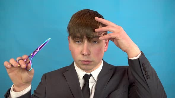 Thumbnail for Businessman Cutting His Own Hair on a Blue Background. A Man in a Suit Has Cut Bangs Scissors