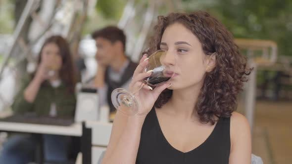 Thumbnail for Cute Young Curly Woman Drinking Red Wine at Street Cafe