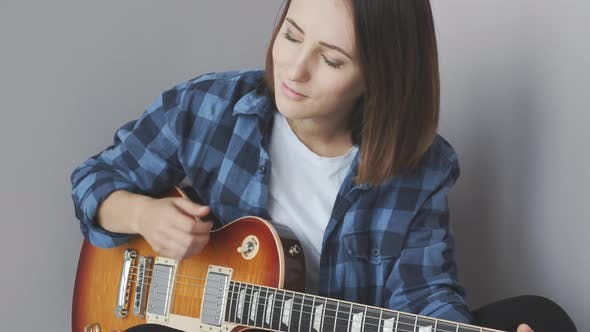 Thumbnail for Woman playing guitar wearing blues shirt enjoying song. Music Industry concept