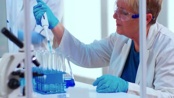Scientist in Medical Laboratory Examinining Drug Discovery Using Micropipette