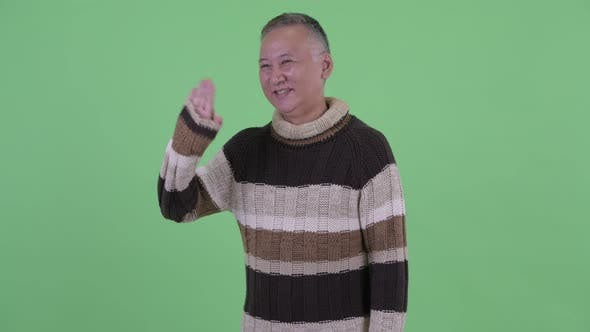 Thumbnail for Happy Mature Japanese Man Waving Hand Ready for Winter
