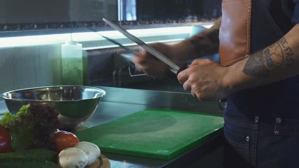 Cover Image for Cropped Shot of a Professional Chef Sharpening His Knife