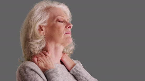 Close-up of elder woman with chronic neck pain looking worried on gray backdrop
