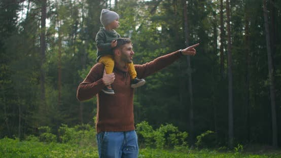 Thumbnail for Slow Motion: Son Sitting on His Fathers Neck in the Spring Sunny Park. Fathers Day