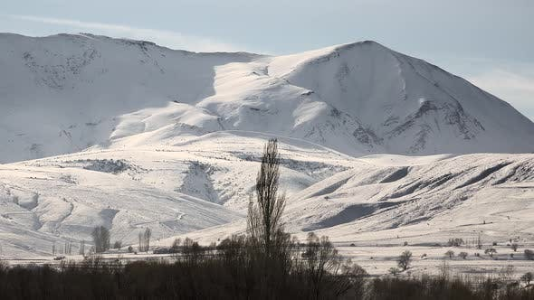 Snowy Mountain Ranges on Edge of Flat Terrain in Sunny Winter