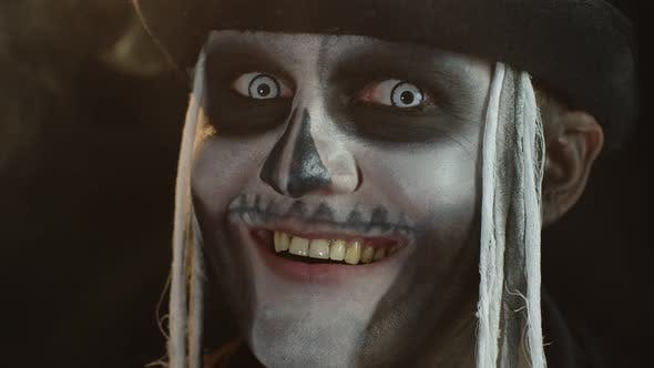 Thumbnail for Close-up of Frightening Man Face with Creepy Skeleton Halloween Makeup Exhaling Cigarette Smoke