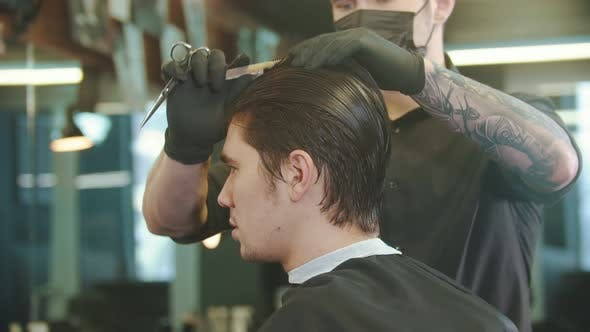 Thumbnail for Barber Putting Client's Hair in Sections for Cutting