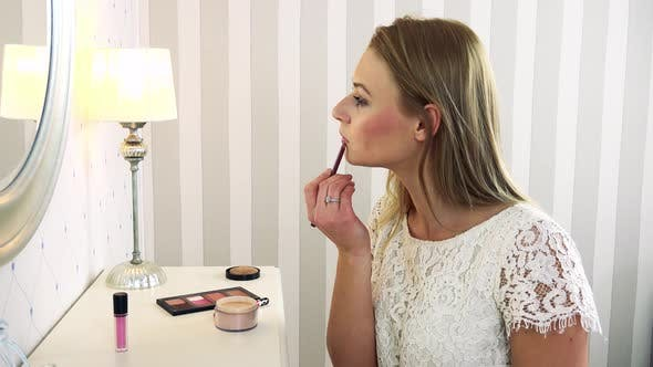 Thumbnail for A Young Attractive Woman Makes Herself Up in Front of a Mirror