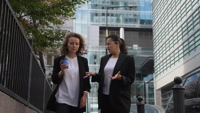 Conversation of Two Business Women Outside Office Buildings