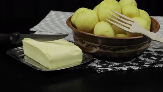 Washed Fresh Raw Potatoes on a Table Ready for Cooking. Butter, Wooden Fork