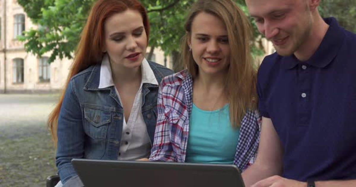 Young People Watch Something on Laptop on Campus