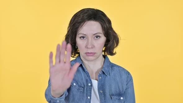Thumbnail for Stop Gesture By Old Woman on Yellow Background