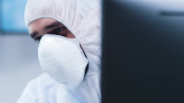 Thumbnail for Dolly Revealing Shot of Biologist in White Coverall Analyzing a Plant Sample
