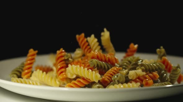 Thumbnail for SLOW MOTION: Cooked Color Spiral Pasta Fall Into White Empty Plate