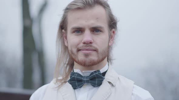 Thumbnail for Close-up Face of Stylish Caucasian Man in White Shirt and Plaid Bow Tie Looking at Camera