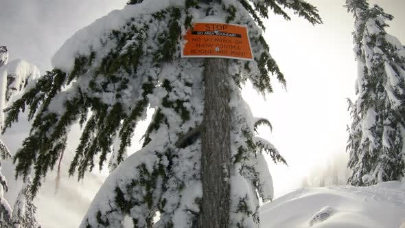 Thumbnail for Pan From Ski Boundary Sign To Snowy Mountain Peaks In Dreamy Backcountry