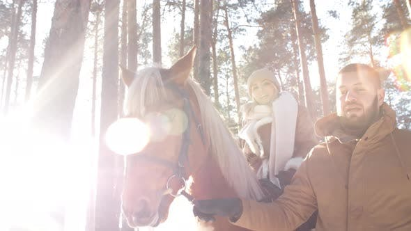 Thumbnail for Woman Riding Horse with Help of Boyfriend in Forest