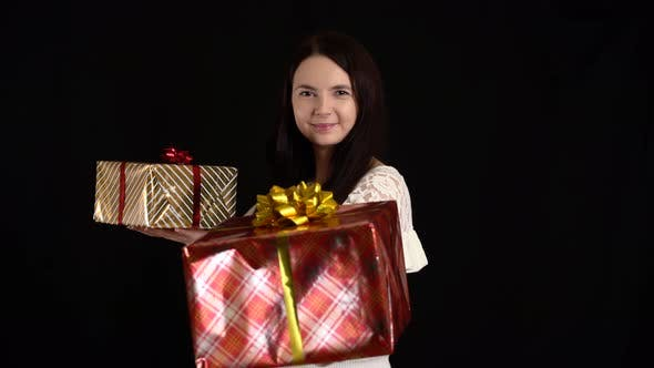 Thumbnail for Young Woman with a Gift Box on Black Background. Gift Box with White Ribbon for Happy New Year