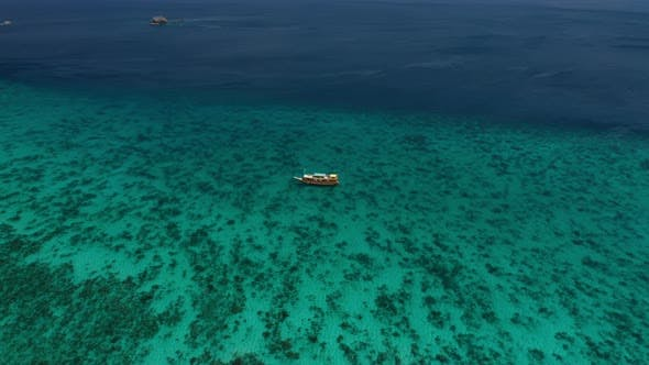 Thumbnail for Drone Over Turquoise Sea With Moored Boat