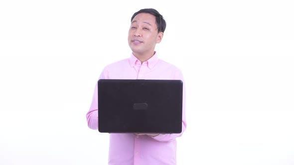 Thumbnail for Happy Japanese Businessman Thinking While Using Laptop