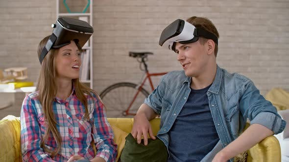 Thumbnail for Young Woman and Man with VR Goggles Chatting