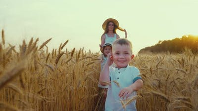 Little Boy Walking in Field with Family