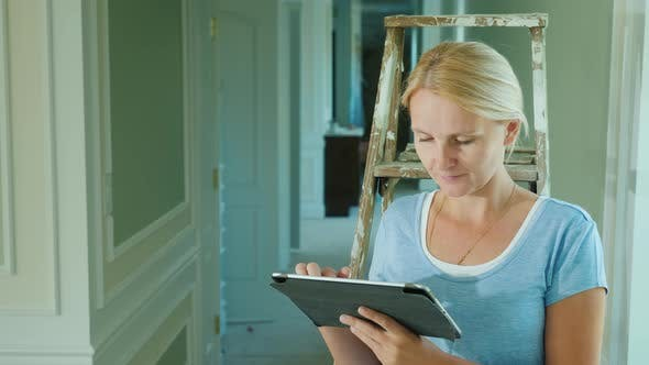 Thumbnail for A Woman Uses a Tablet in the House Where Repairs Are Underway. Online Order of Building Materials