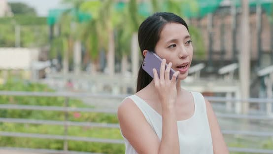 Woman talk to cellphone in city