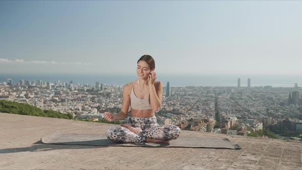 Thumbnail for Woman in Earphones Listening Music on Smartphone. Woman Meditating in City