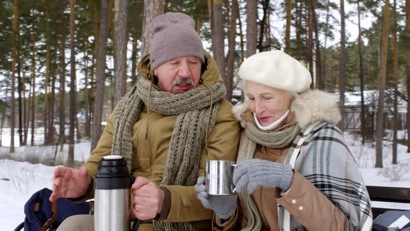Thumbnail for Happy Elderly Couple Enjoying Hot Tea on Bench in Winter