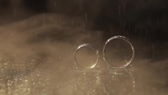 Thumbnail for Wedding Rings on Dark Water Surface Shining with Light. Water Drops. Close Up