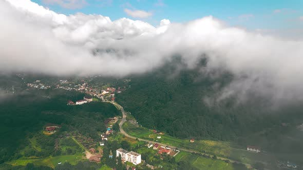 Aerial View Flight Over the Clouds Through Which You Can See the Village Between the Mountains. View